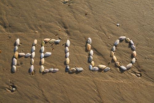 'Hello' spelt in shells on a beach